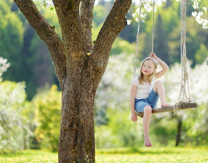 Pige sidder i gynge under stort træ