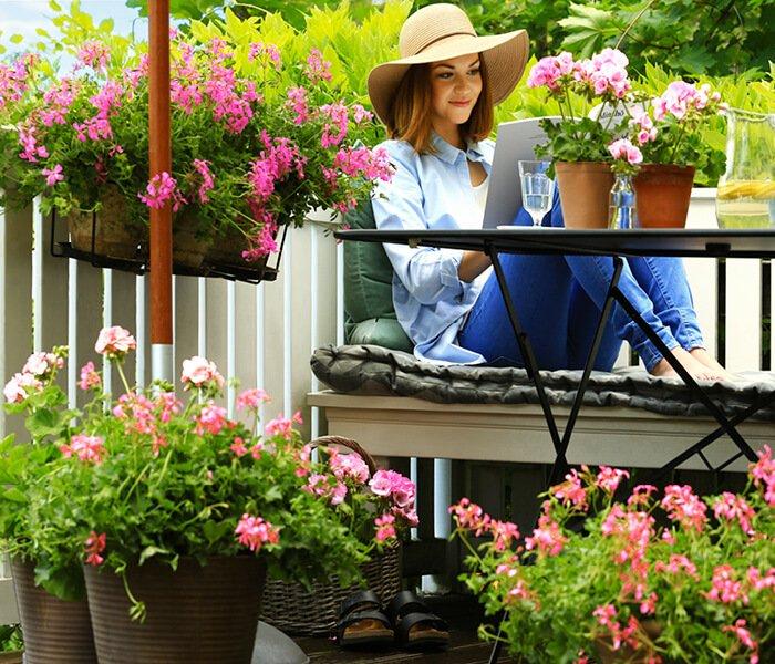 Kvinde slapper af på blomstrende terrasse